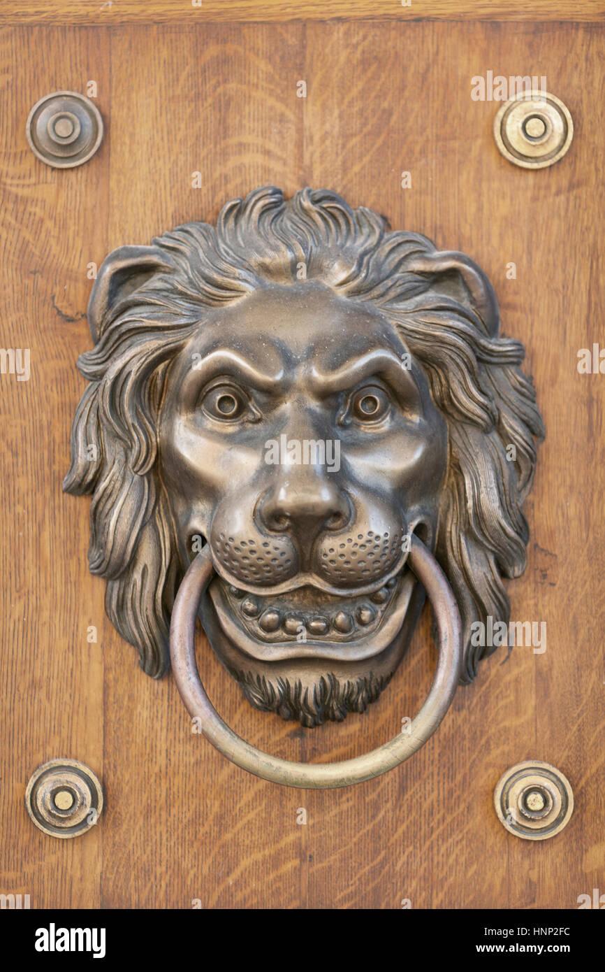 An antique brass lion-head door knocker set in a wood door. - Stock - Lion Head Door Knocker Stock Photos & Lion Head Door Knocker Stock
