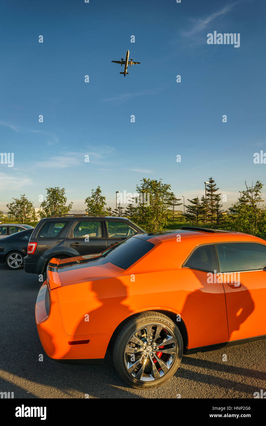 Orange Ford Mustang with plane overhead, Reykjavik, Iceland - Stock Image