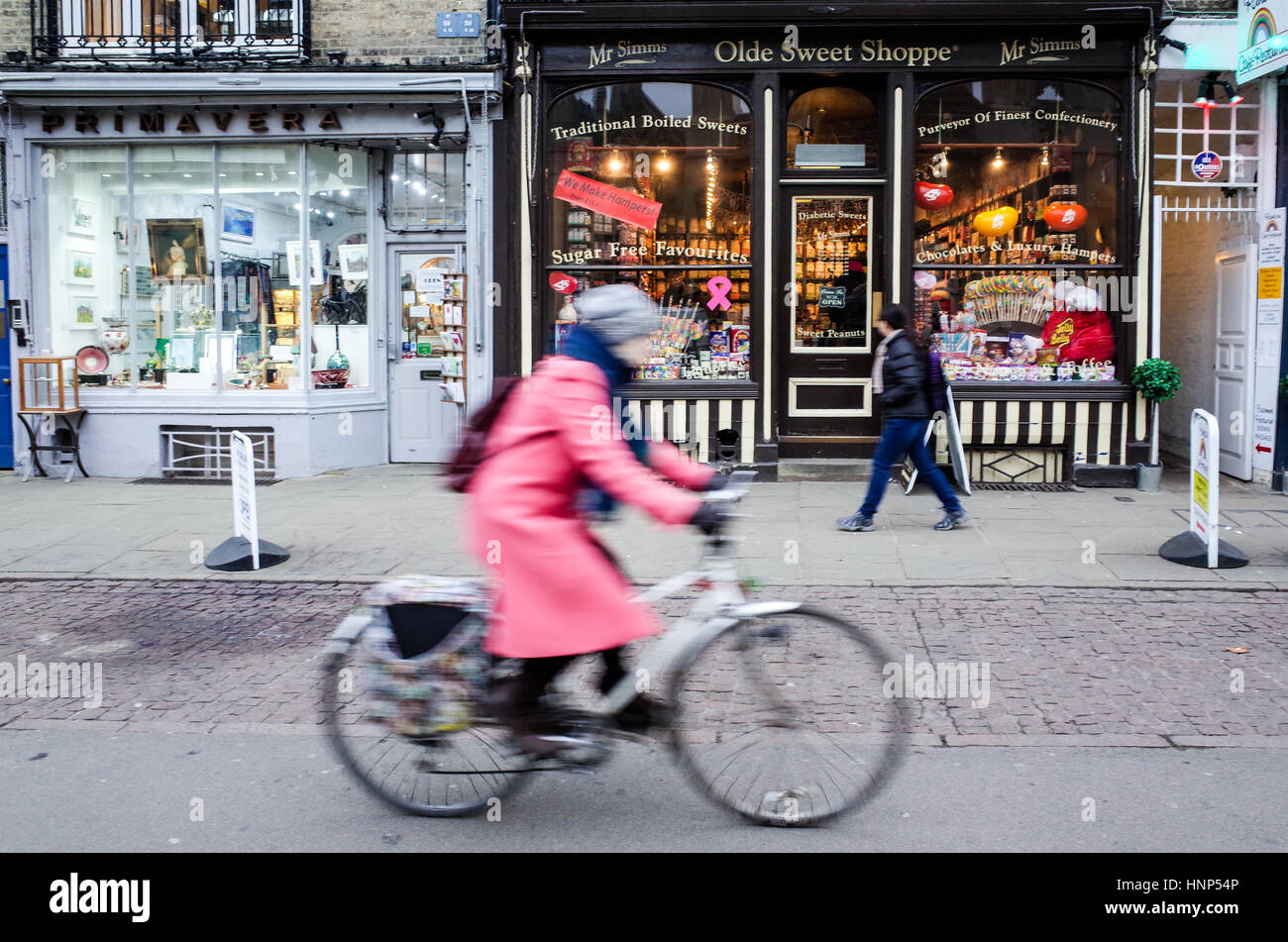 A woman cycles past independent shops in Kings Parade, Cambridge. Motion Blur. - Stock Image