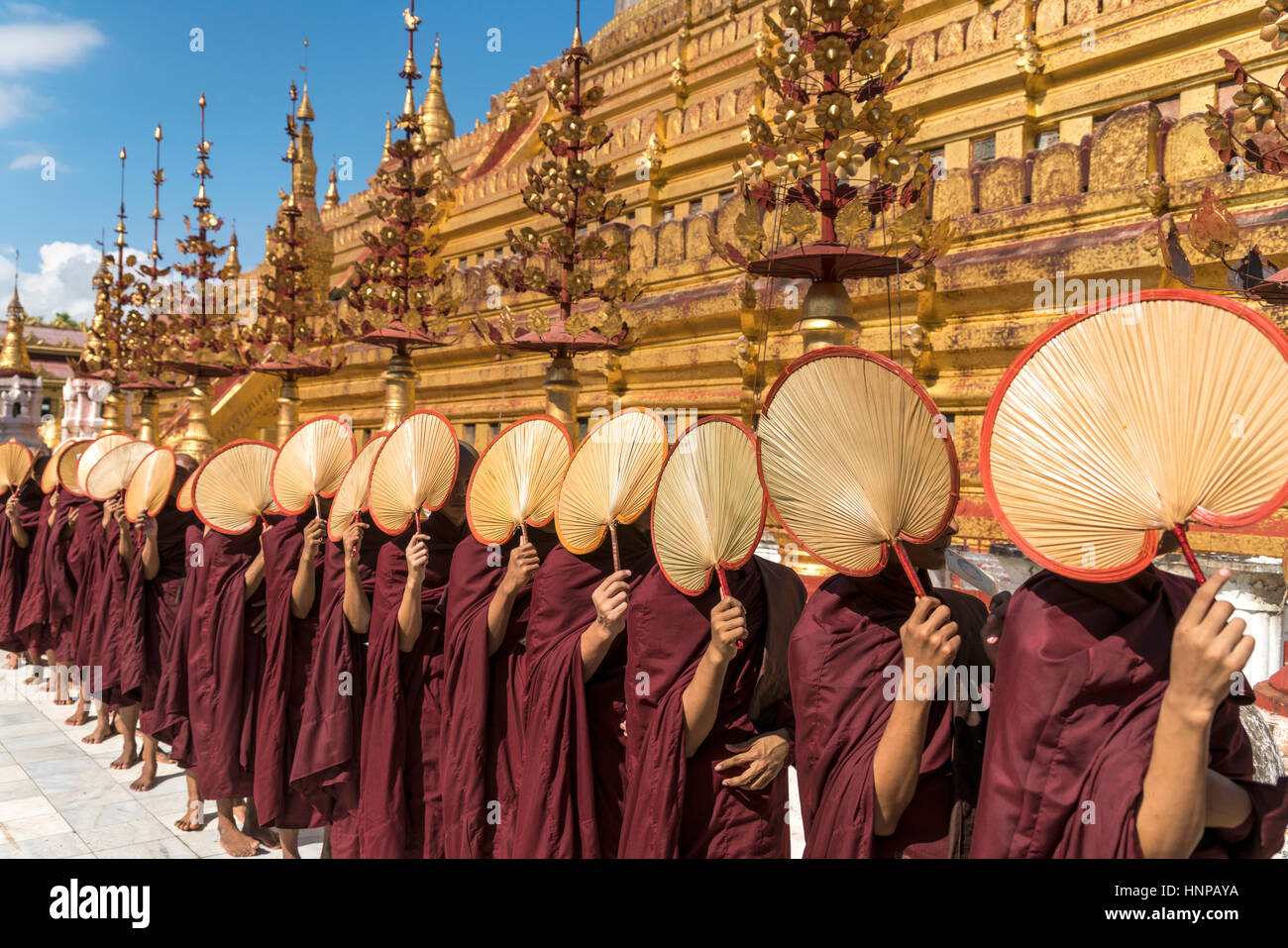 Monks with fans waiting for donations, Shwezigon Pagoda, Bagan, Myanmar - Stock Image