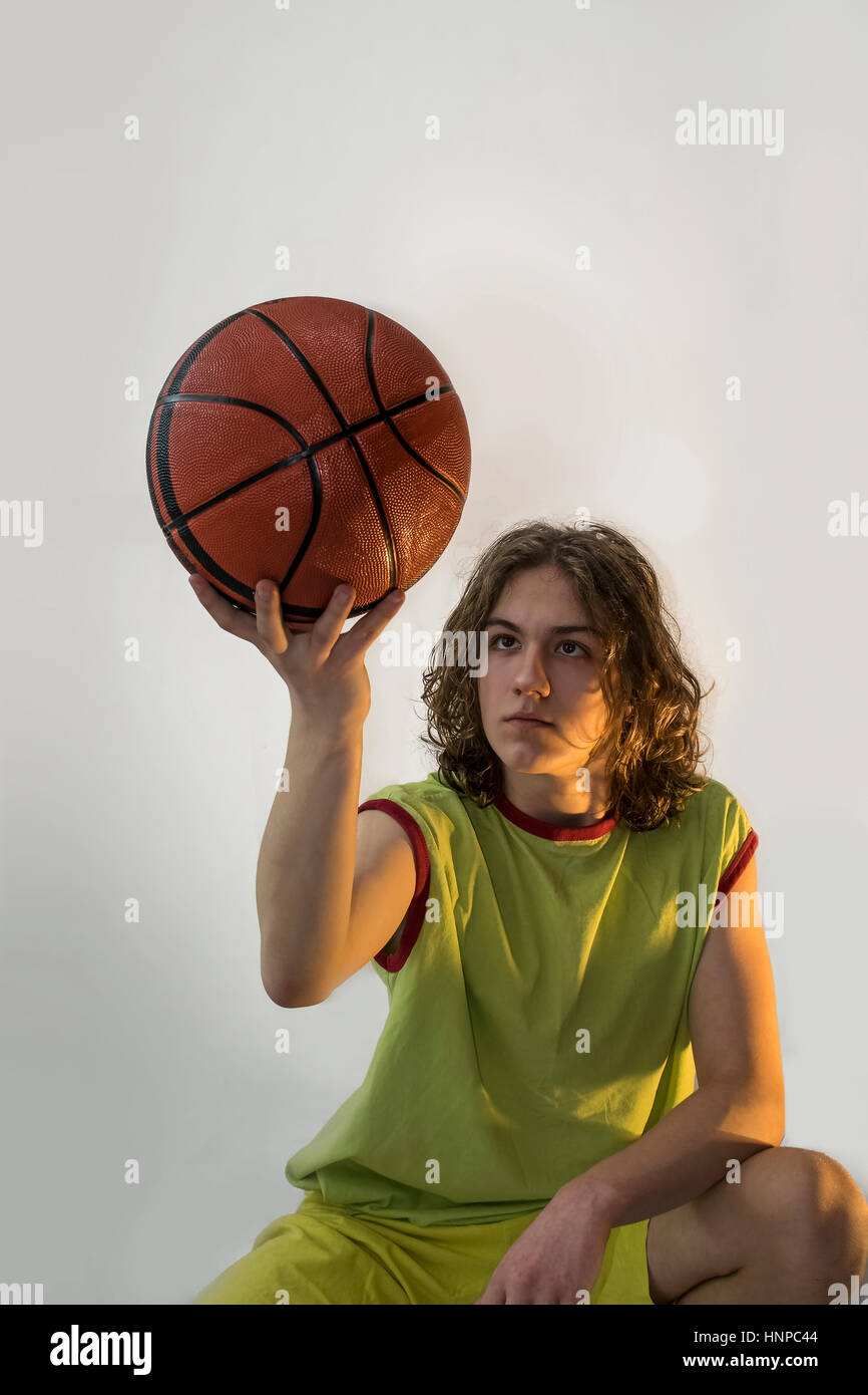 Young boy with long blond hair holding up and looking at a basketball while sitting down. - Stock Image