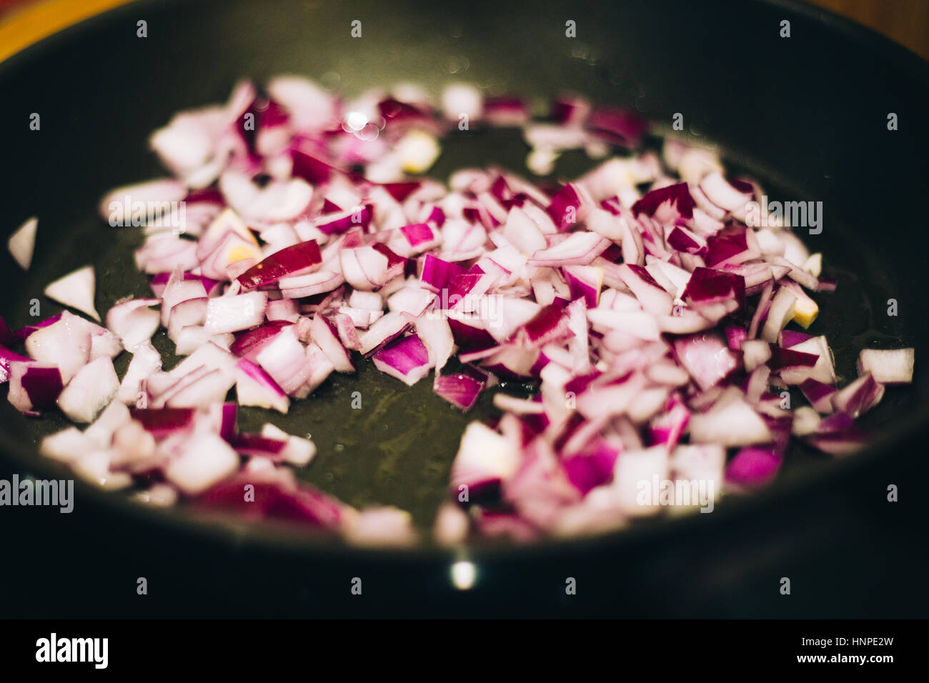chopped red onion in a frying pan - Stock Image
