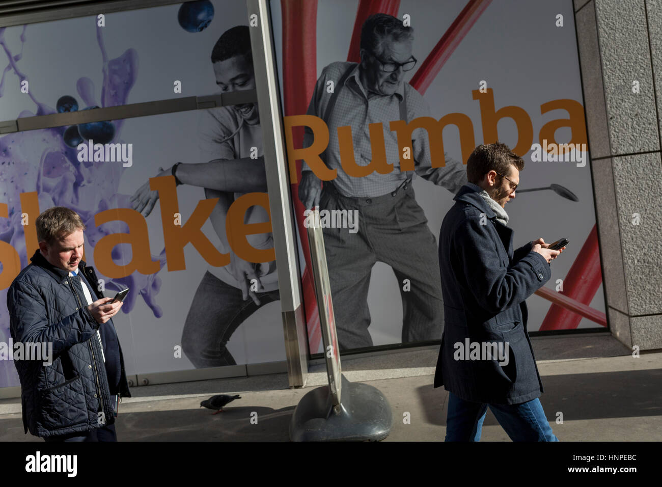 Two men walk and check social media, in front of a Sainsbury's poster, on 13th February 2017, in the City of - Stock Image