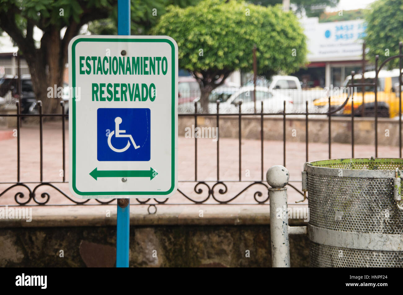 A sign for handicapped parking next to a trash can in the middle of the city. - Stock Image