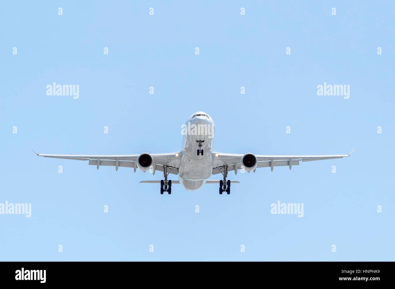 Fully white plane Airbus A330, of Iberia airline, is landing. Spanish company. Blue sky. Sunny day. - Stock Image