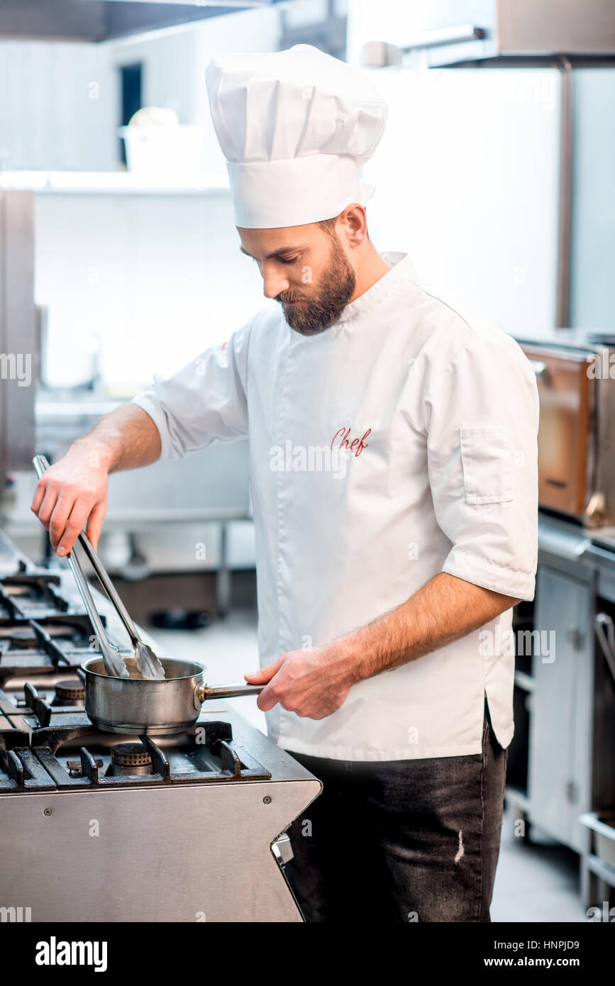 Portrait of chef cook in uniform with knifes at the restaurant kitchen - Stock Image