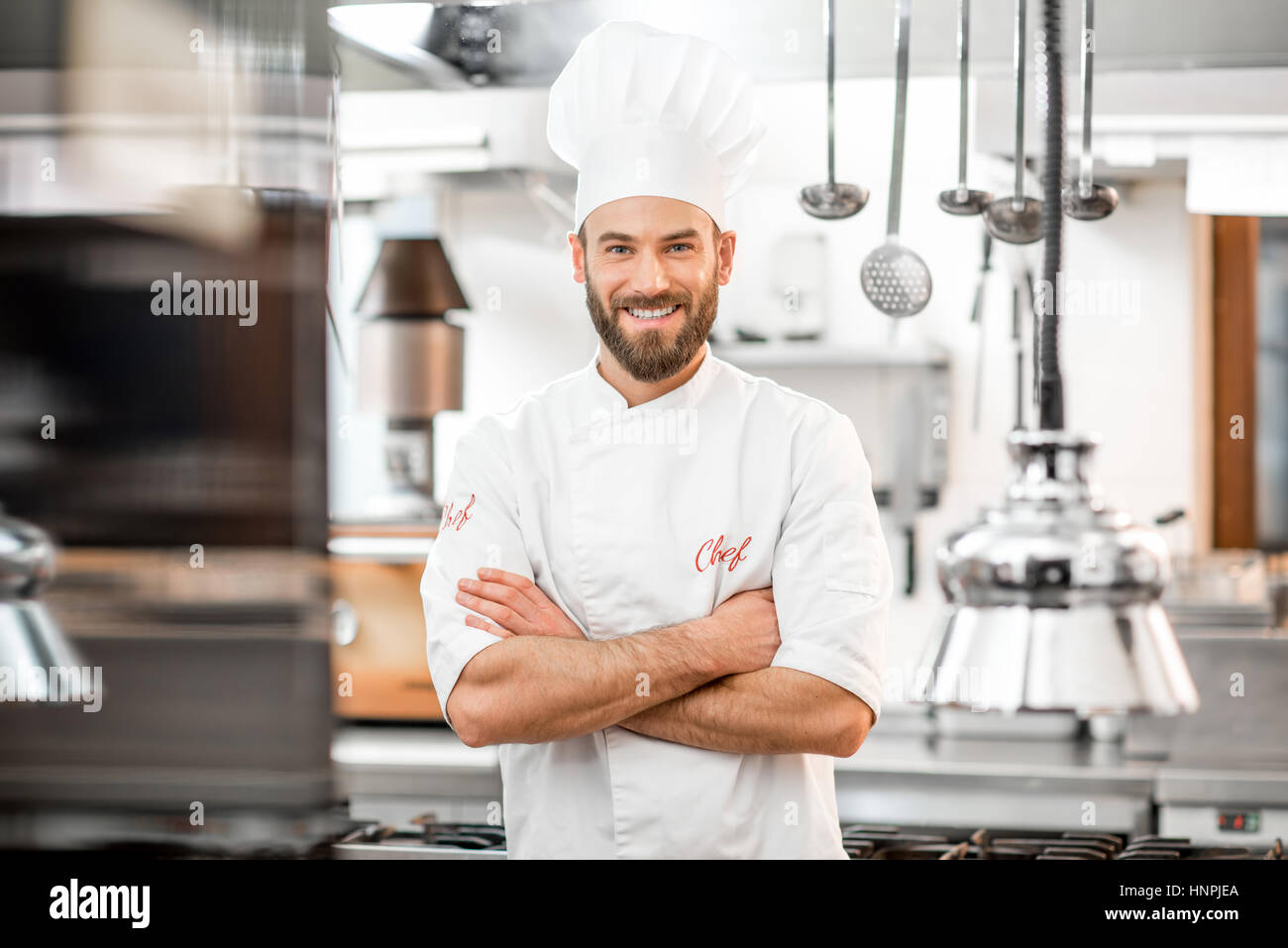 Portrait of handsome positive chef cook at the restaurant kitchen - Stock Image