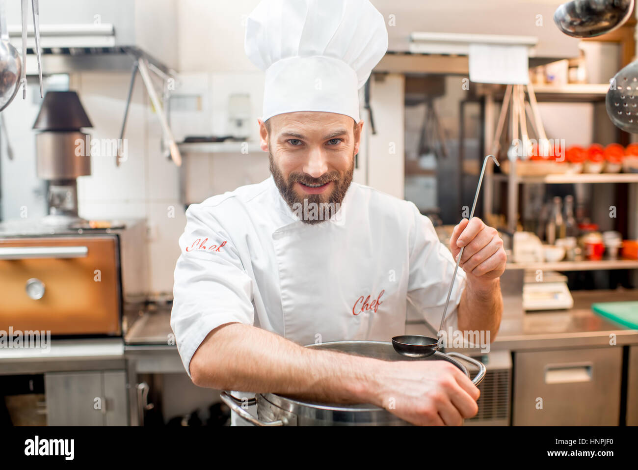 Portrait of a chef cook in uniform with big cooker at the restaurant kitchen - Stock Image