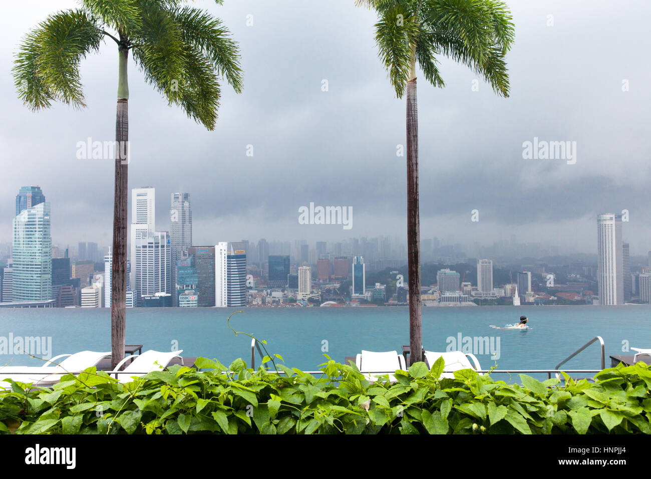 Girl swims in Infinity Pool on the roof of Marina Bay Sands Hotel on July 9, 2013 in Singapore. - Stock Image