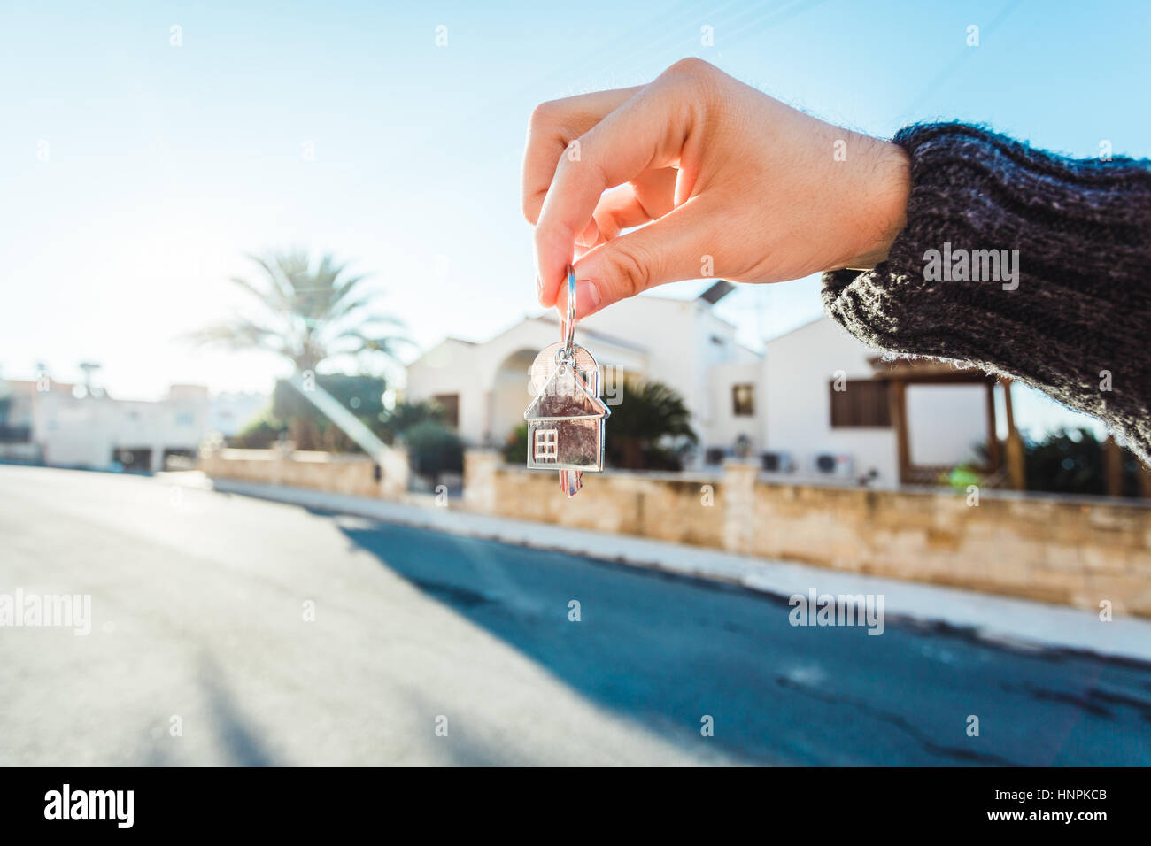Holding house keys on house shaped keychain closeup in front of a new home - Stock Image