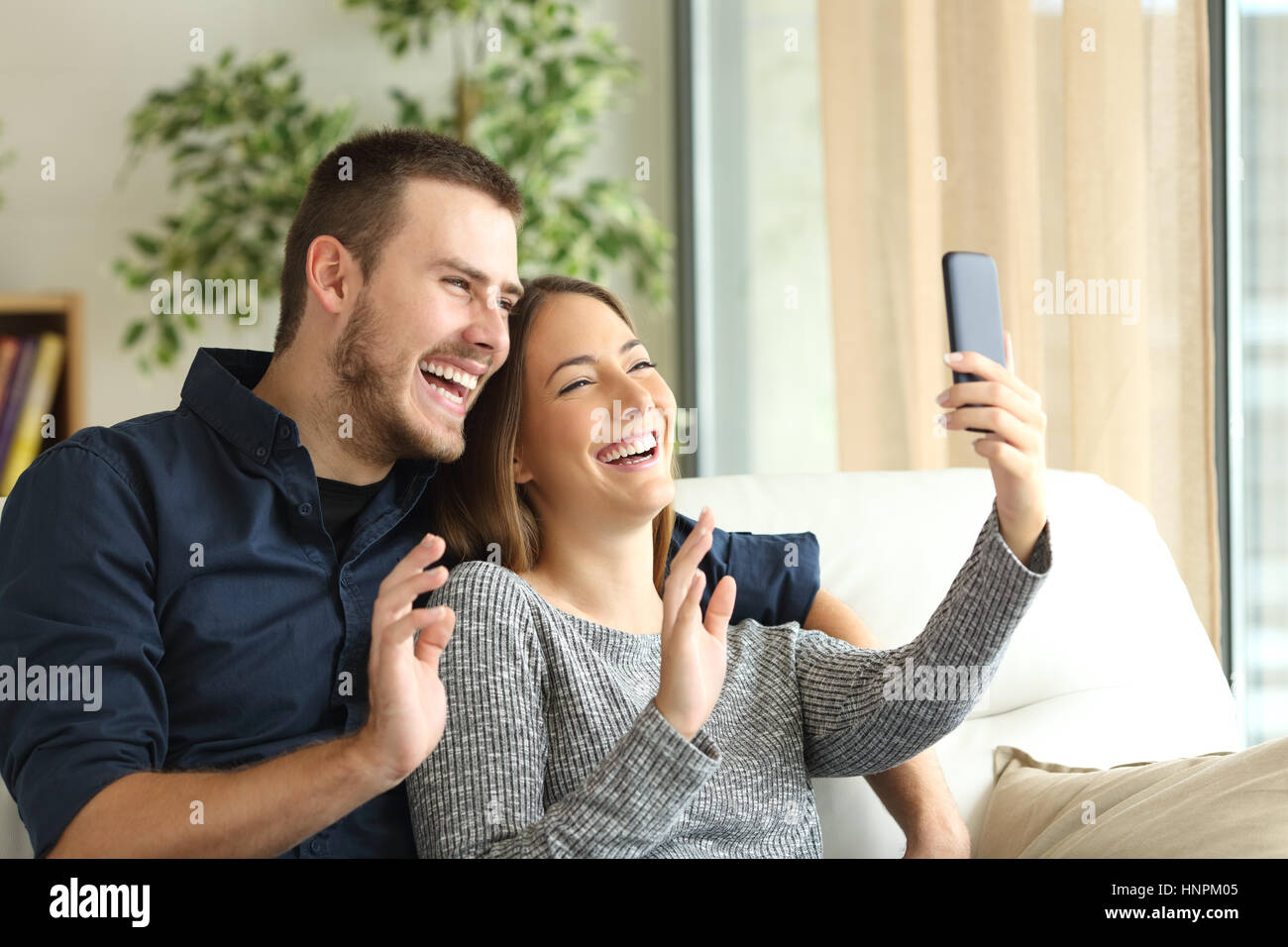 Happy casual couple greeting in a phone video call on line sitting happy casual couple greeting in a phone video call on line sitting on a sofa in the living room at home with a window in the background m4hsunfo