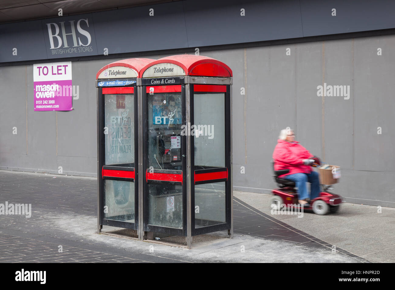 Senior, Pensioner disabled person using mobility scooter passing BT Disused, dirty, redundant red BT KX100 Telephone - Stock Image