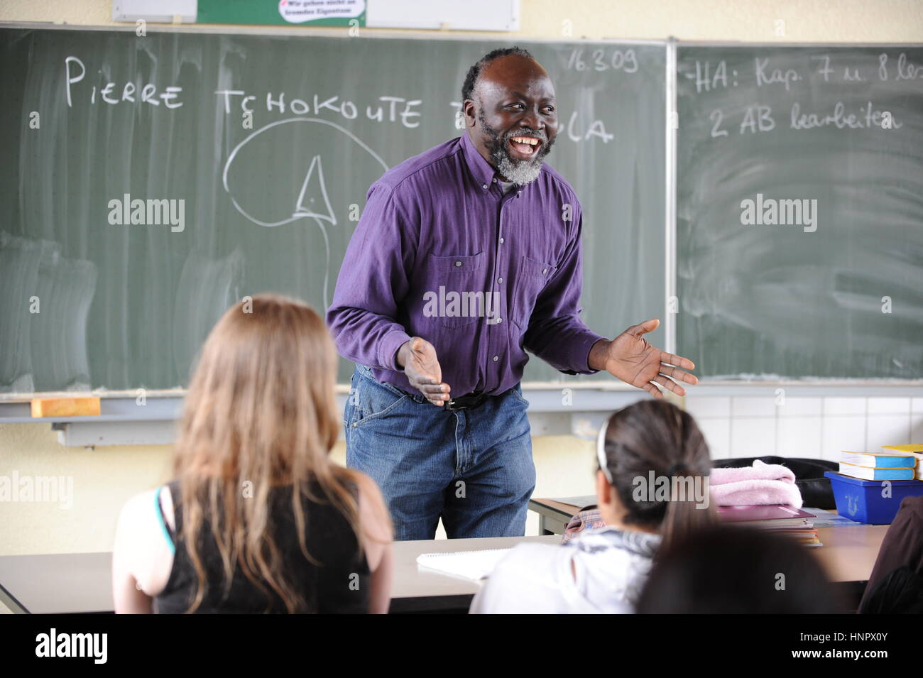 Munich, Germany - August 9, 2013 - Teacher immigrated from africa helping foreign pupils getting integrated in Germany - Stock Image