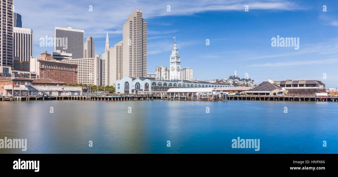 Panoramic view of San Francisco skyline with historic Ferry Building at famous Embarcadero street on a sunny day - Stock Image