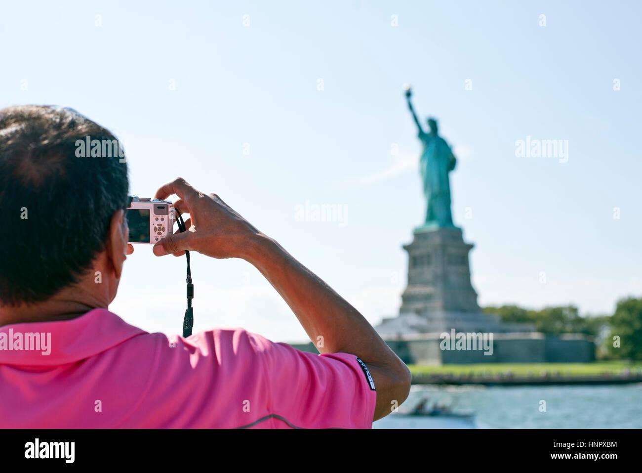 Tourist photographing Statue of Liberty, New York, USA - Stock Image