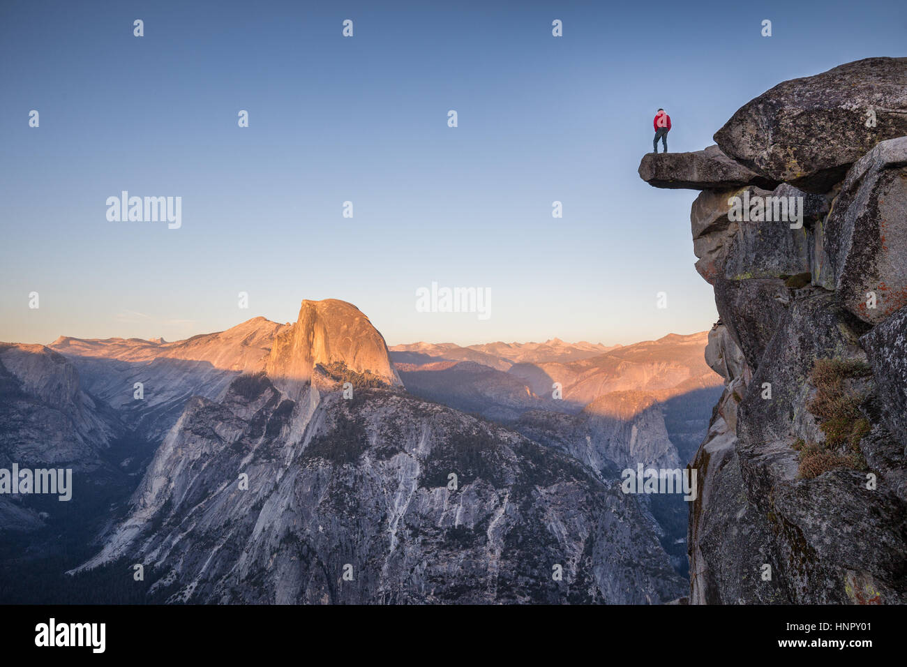 A male hiker standing on an overhanging rock at Glacier Point enjoying the breathtaking view towards famous Half - Stock Image