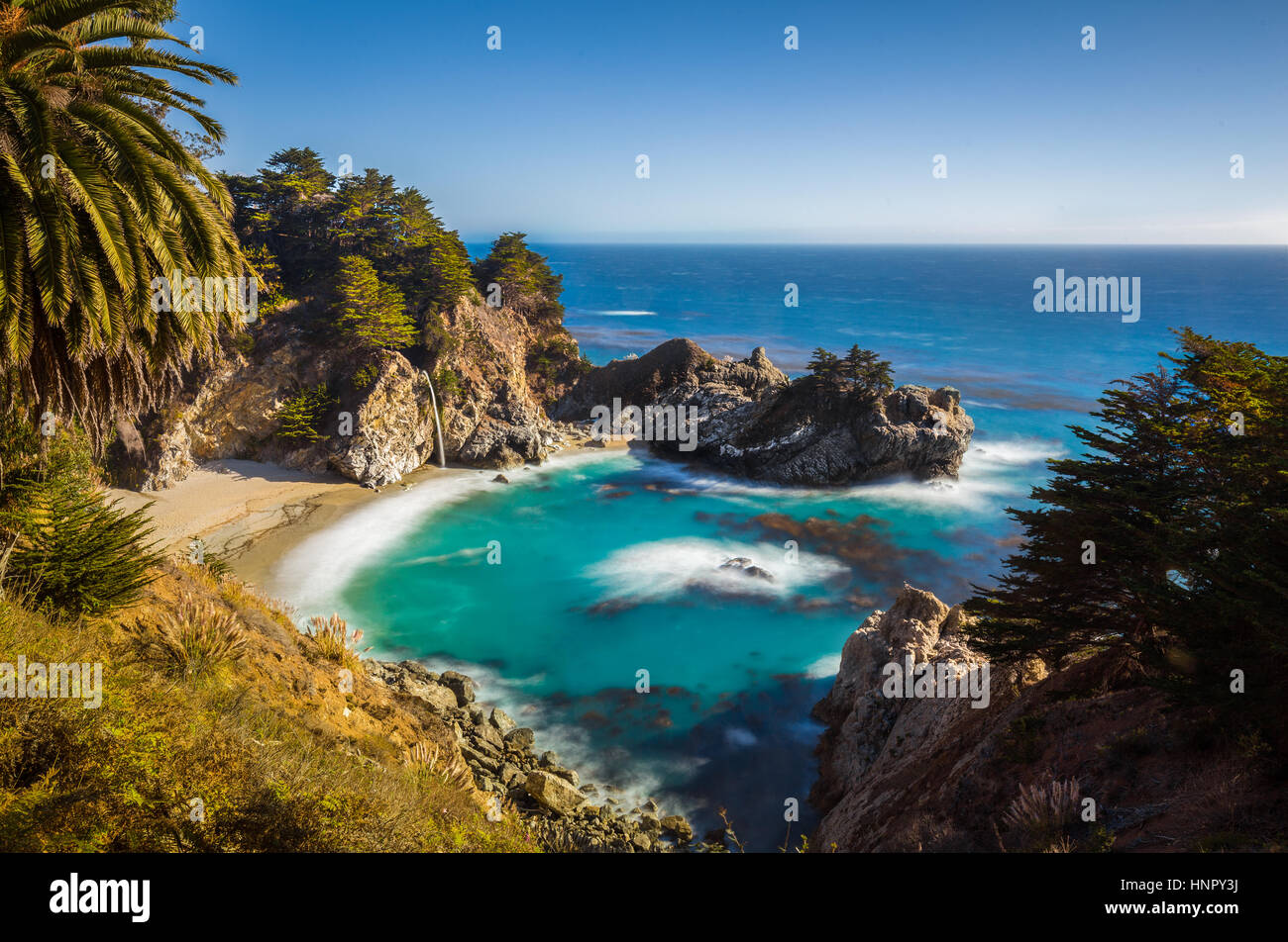 Classic postcard view of famous McWay Falls in golden evening light at sunset on a beautiful sunny day with blue - Stock Image