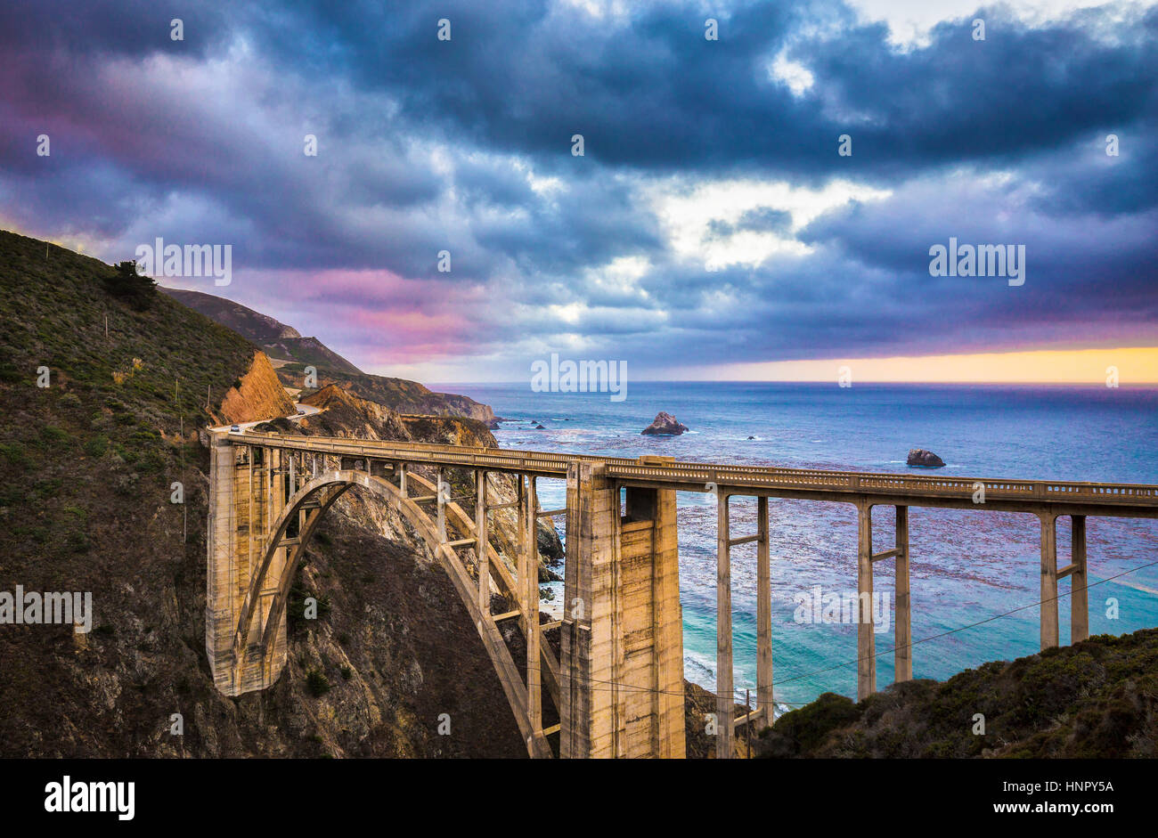 Scenic panoramic view of historic Bixby Creek Bridge along world famous Highway 1 in evening twilight with dramatic - Stock Image