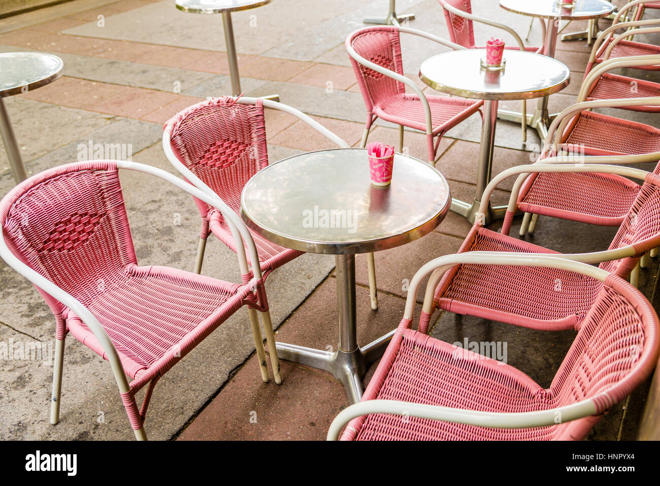 Pink Plastic Wicker Chairs And Round Silver Tables With Pink Cups  Containing Sugar Outside A Bistro.