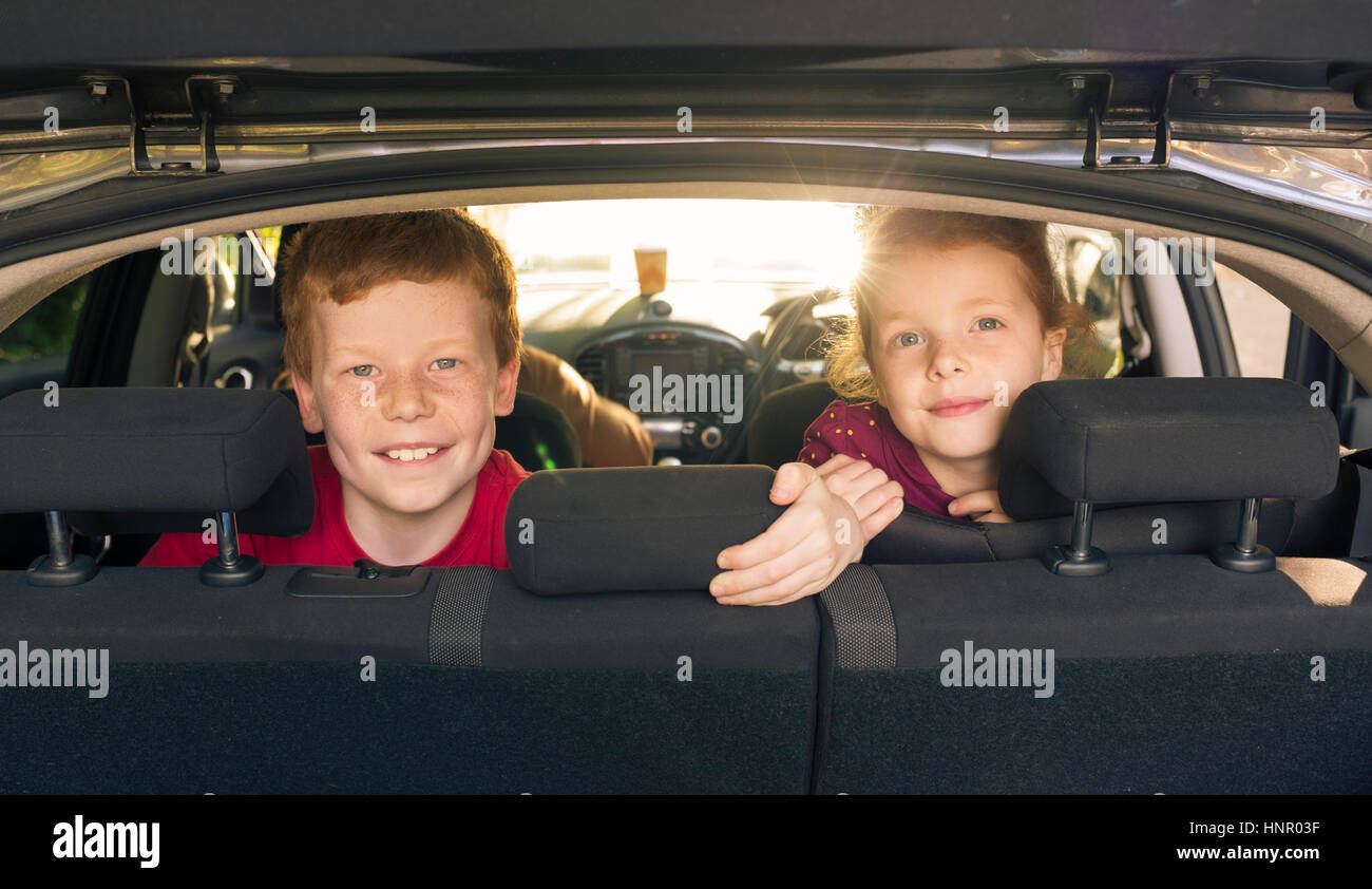 Children looking through the hatchback opening in a car - Stock Image