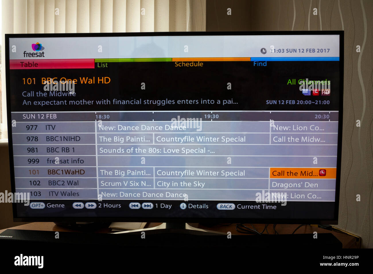 Setting a future programme  recording on a  Freesat Television using the All Channels guide - Stock Image