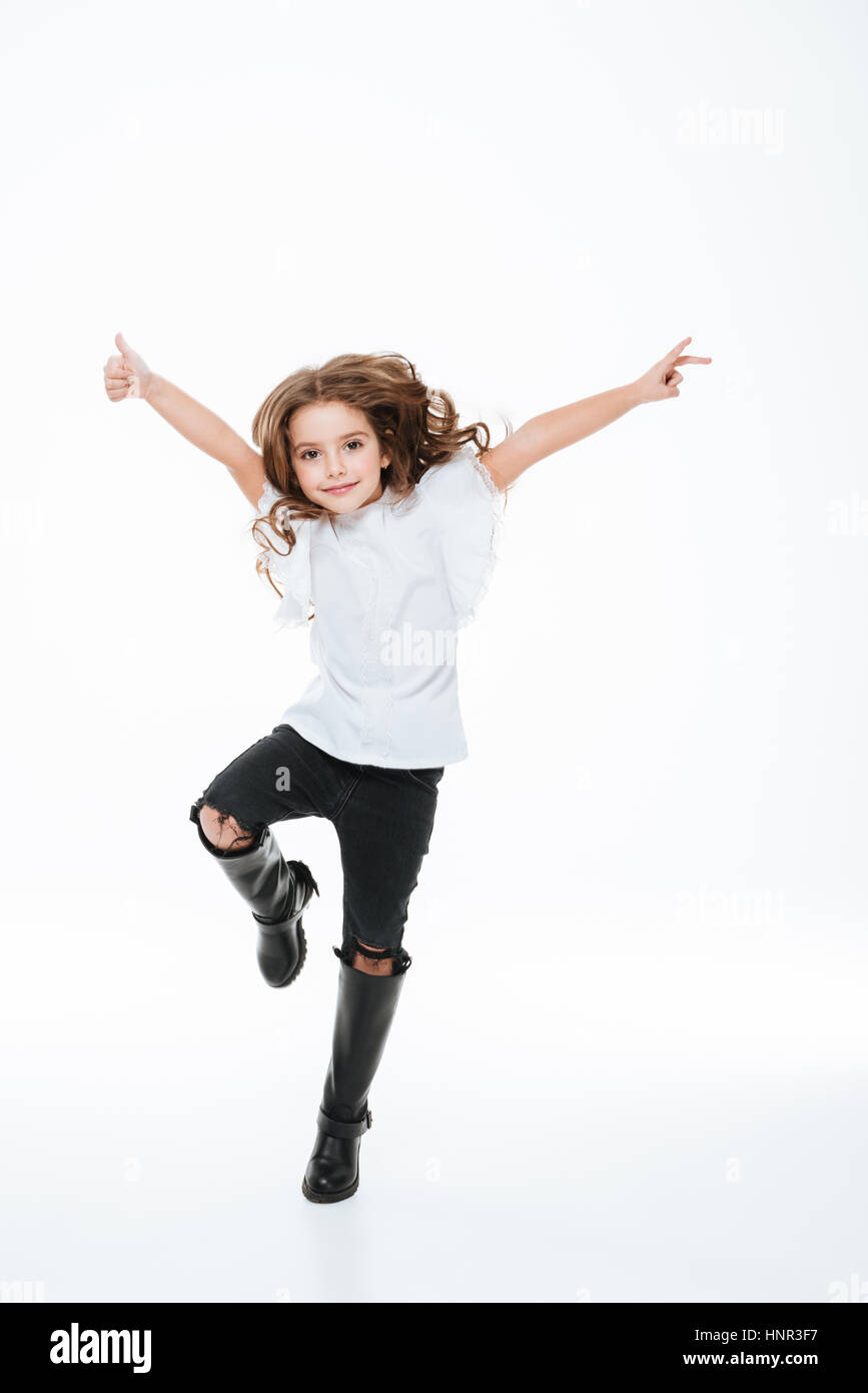 Full length of happy little girl jumping in the air over white background - Stock Image