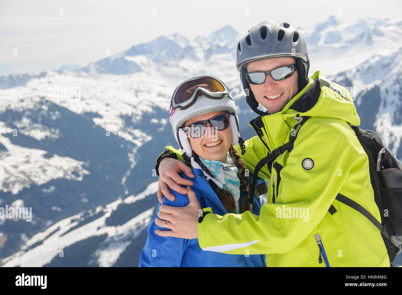 Winter sport active couple portrait  in embrace on the top of mountain in ski resort. Winter vacation with snow - Stock Image