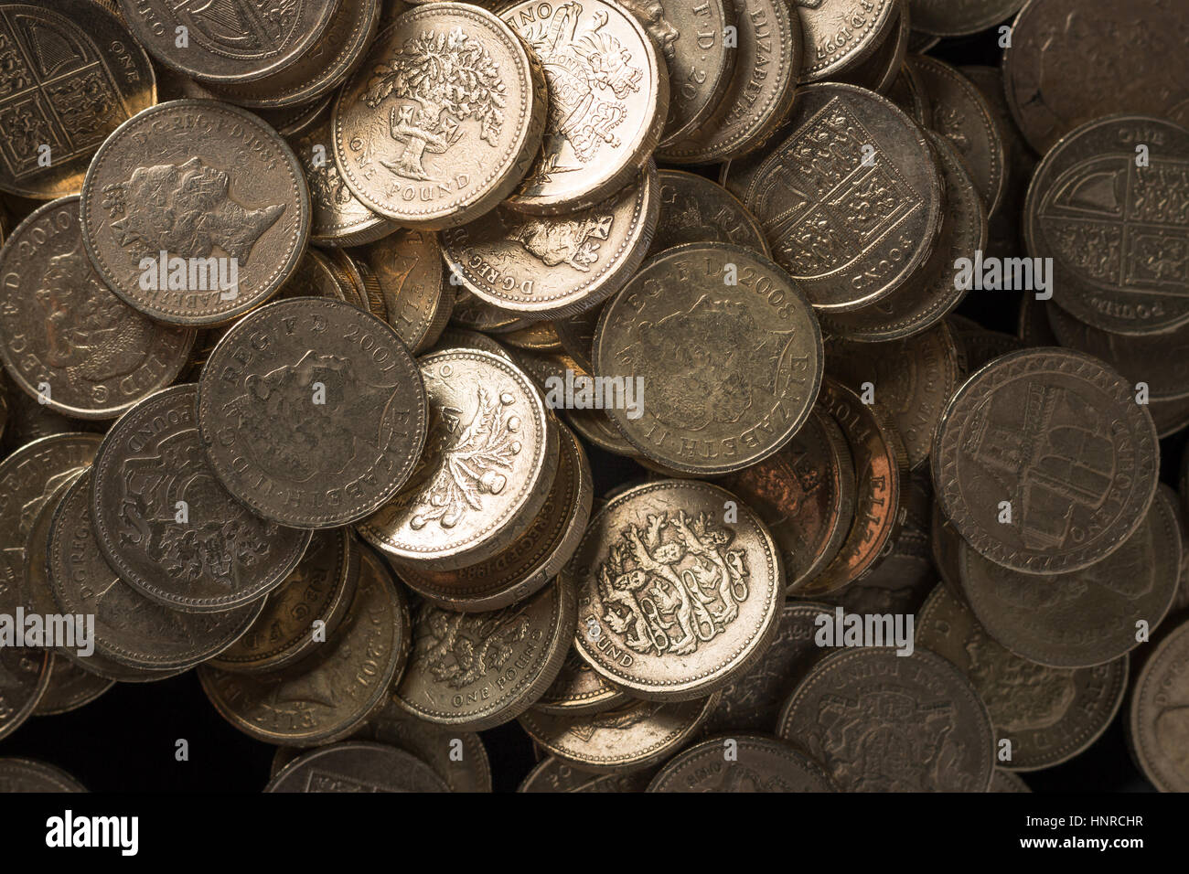 Stacks of pound coins arranged in piles. - Stock Image