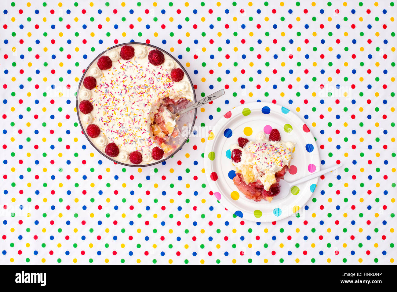 Trifle on a colourful polka dot plate and table cloth - Stock Image