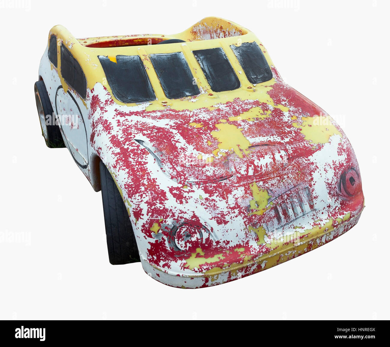 Weather-beaten child's red and yellow play car. Isolated. Stock Photo