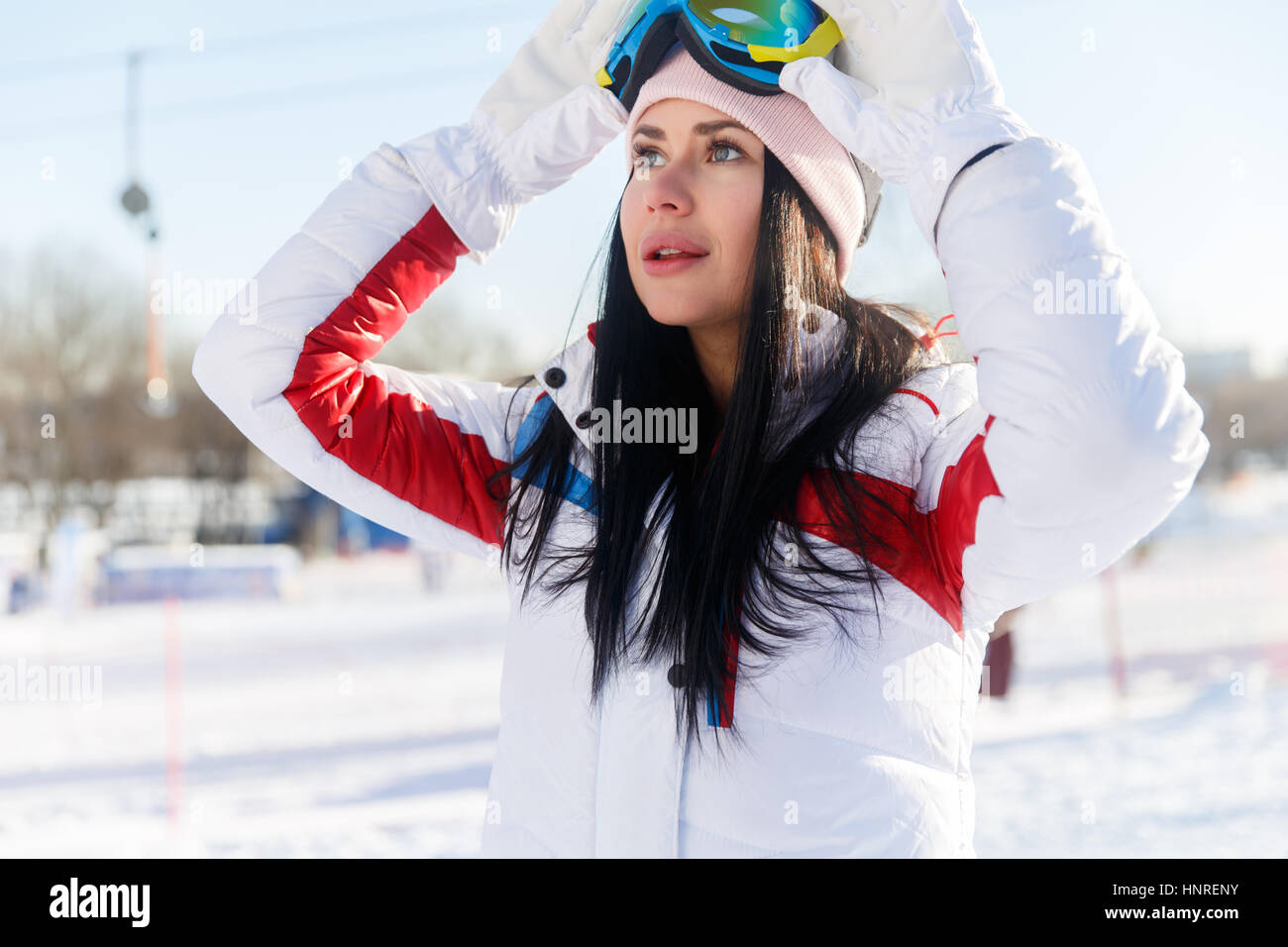 Long-haired woman in ski suit on winter weekends - Stock Image