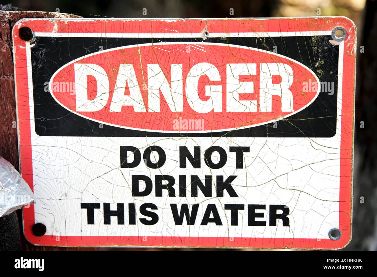 Faded DANGER DO NOT DRINK THIS WATER sign. Stock Photo