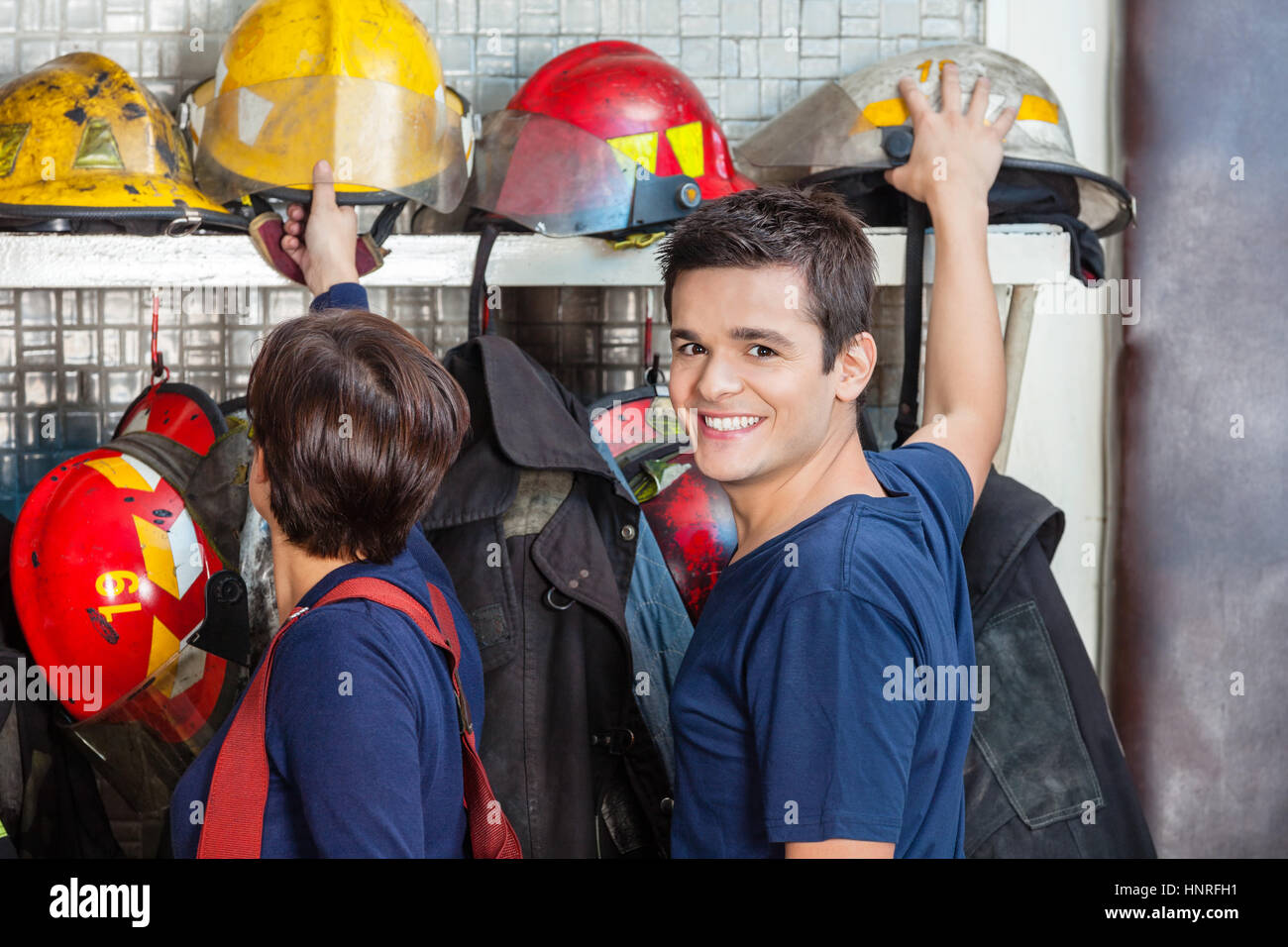 Happy Firefighter With Colleague Removing Helmet - Stock Image