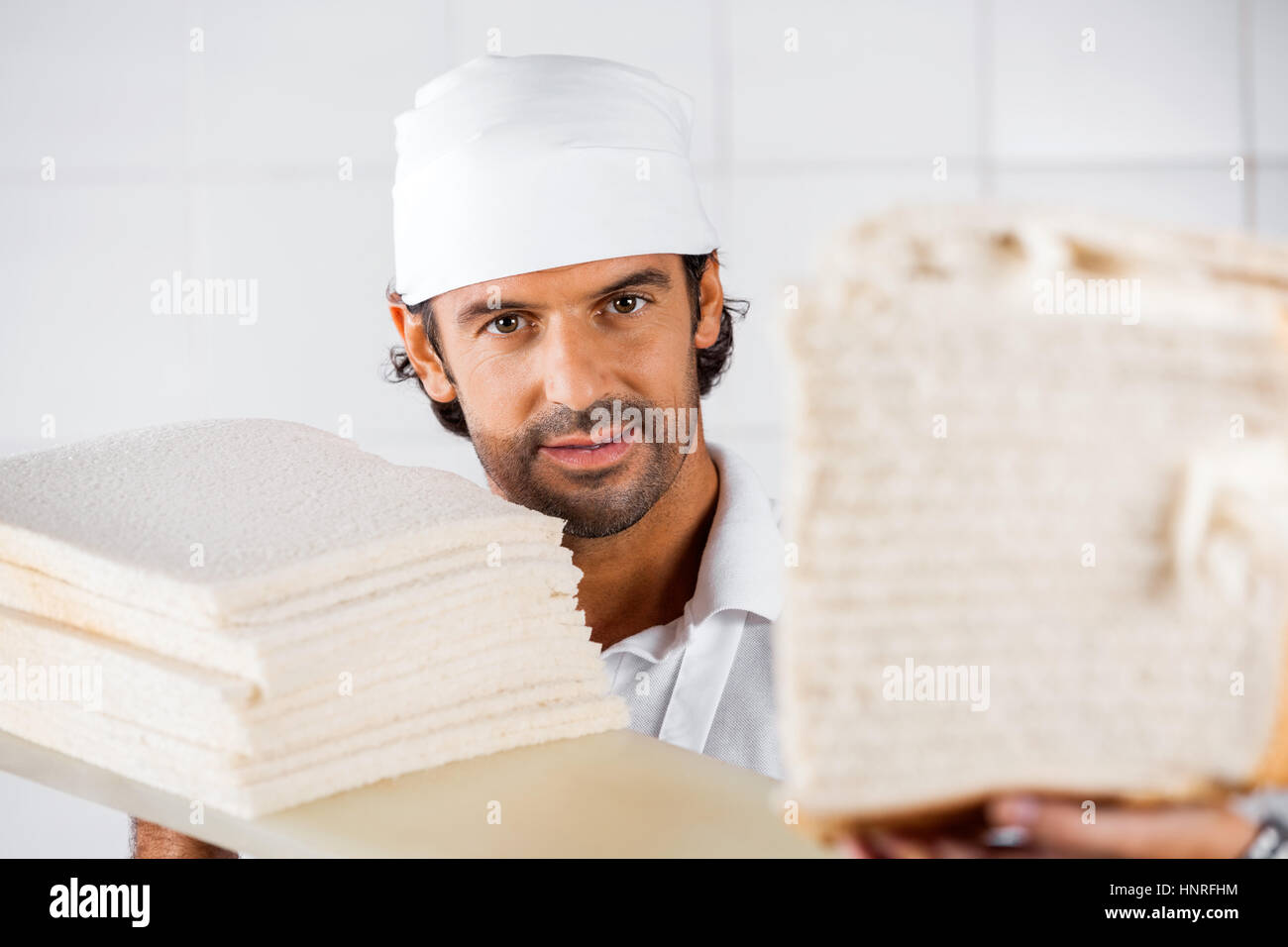 Confident Male Baker With Bread Slices - Stock Image