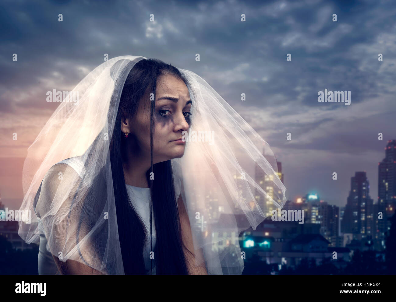 Young tearful bride on the background of night city - Stock Image