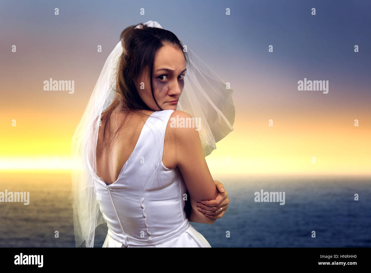 Tearful bride on the background of the sea and sunset - Stock Image
