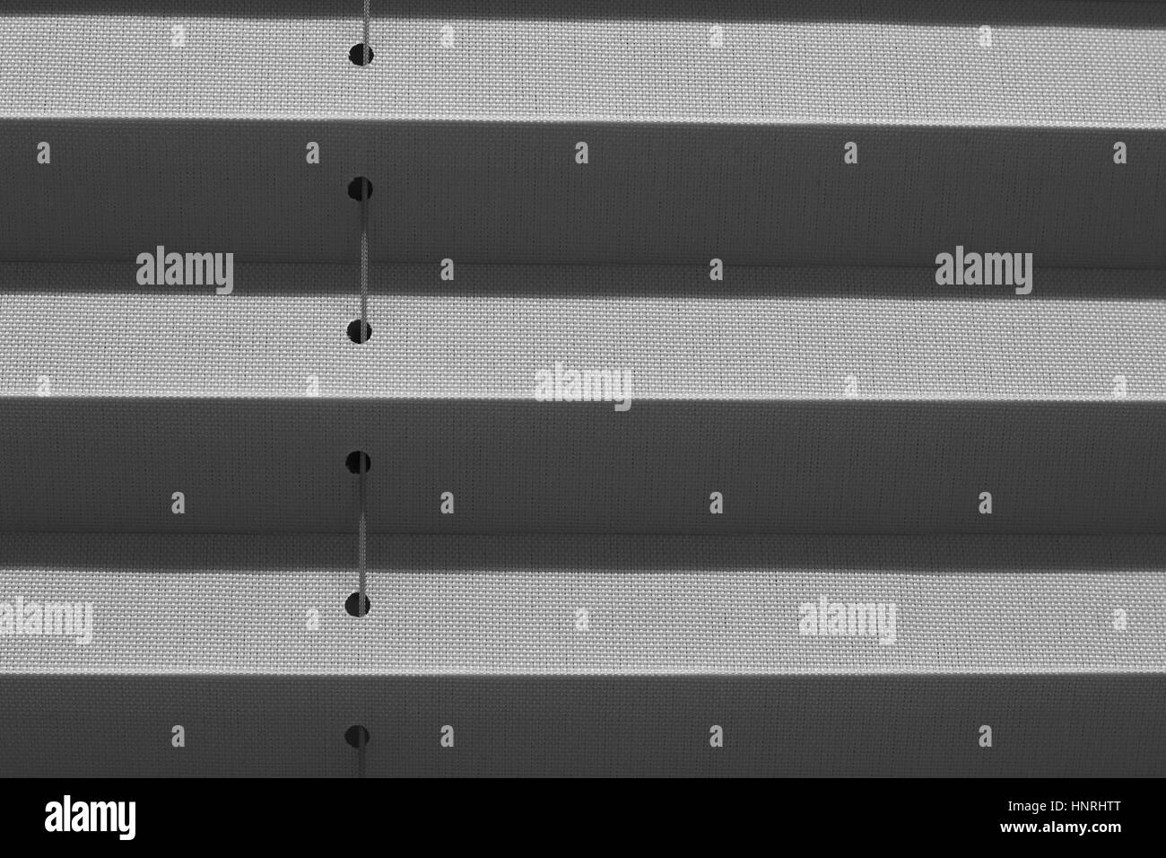 Window gray pleated blind close up with details in home interior. Structure and texture of fabric background. - Stock Image