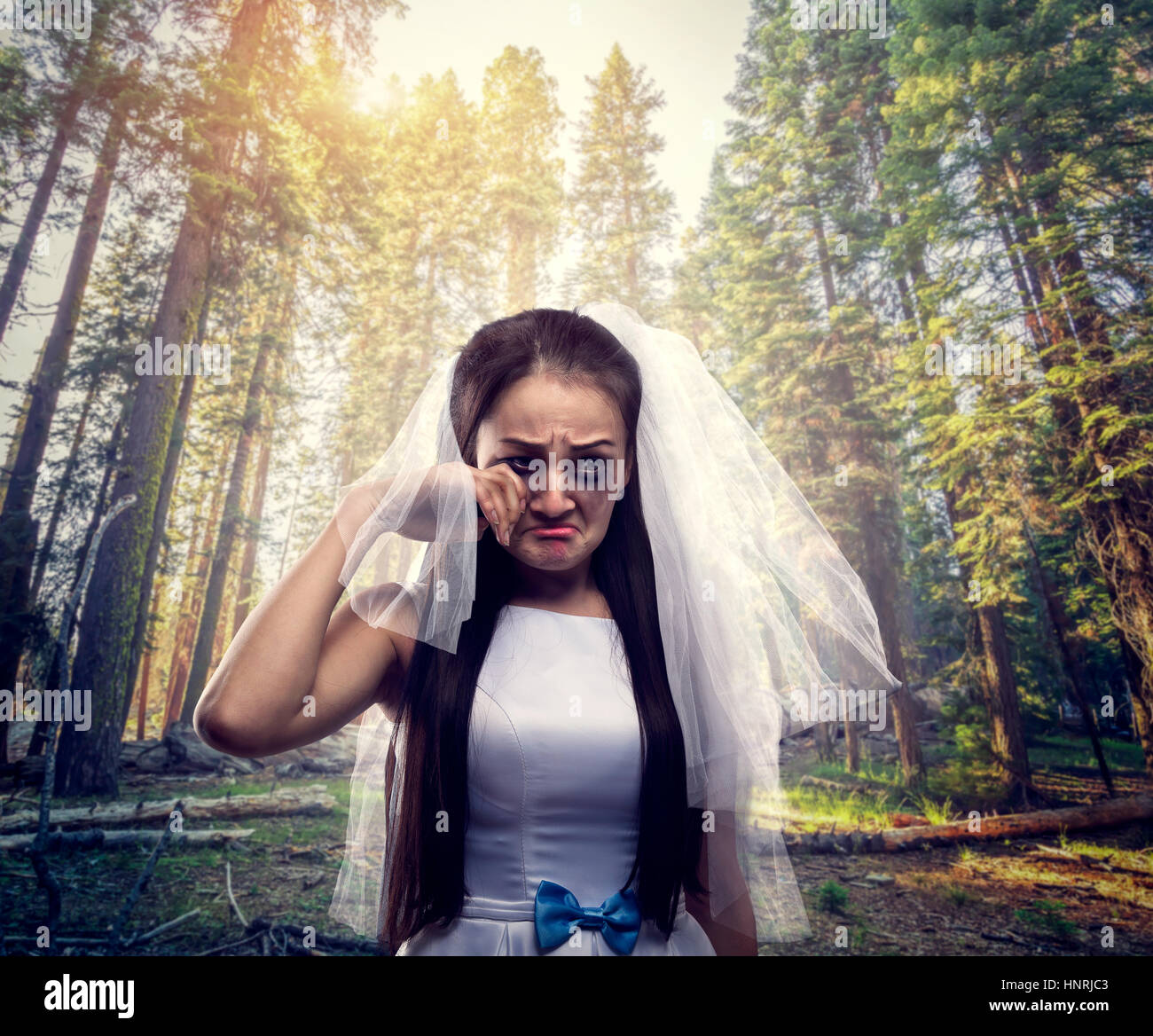 Bride with tearful face, pine forest on background. Unhappy marriage - Stock Image
