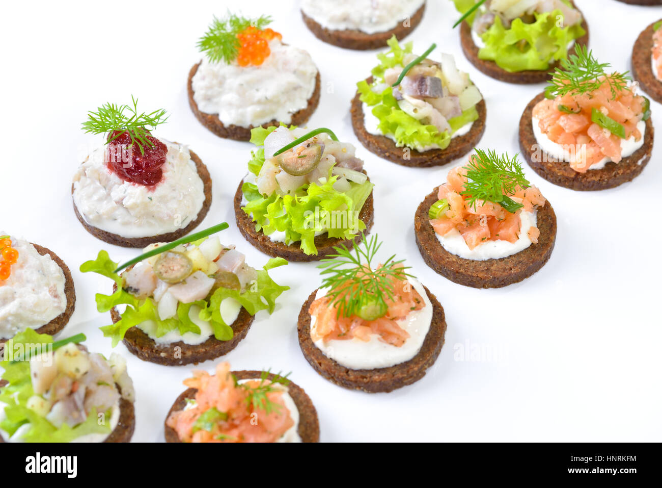 Tasty fish finger food  with smoked salmon tartar, trout mousse with caviar and herring salad on round pumpernickel - Stock Image