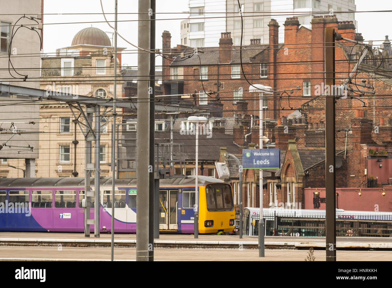 Leeds cityscape.  Leeds railway train station platform with overhead wires,and typical housing and building styles Stock Photo