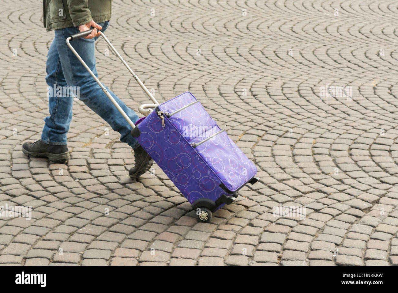 male tourist pulling wheeled suitcase over cobbles - Stock Image