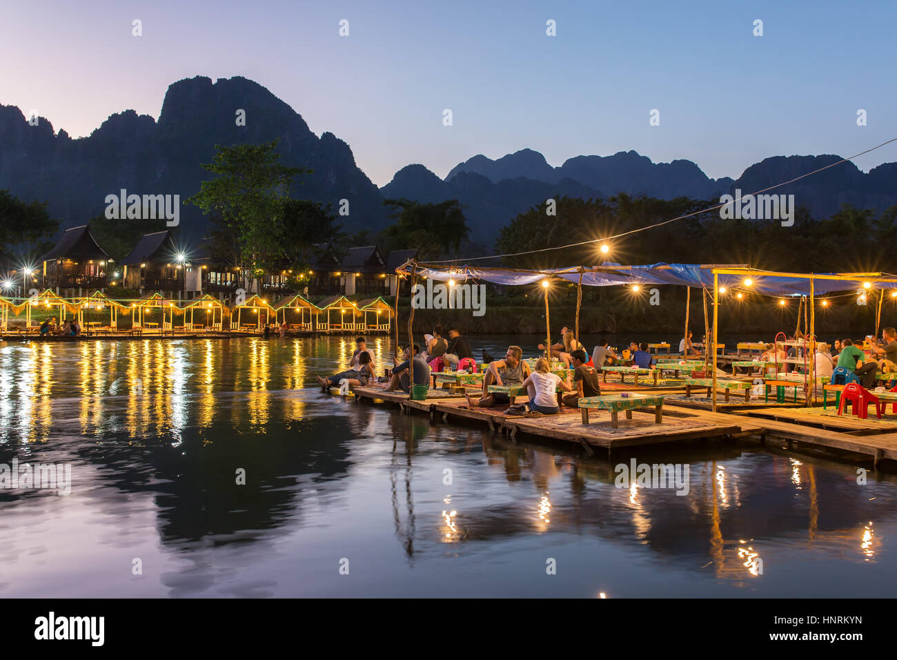 Vang Vieng, Laos - January 19, 2017: Restaurant on the riverfront during sunset in Vang Vieng, Laos - Stock Image