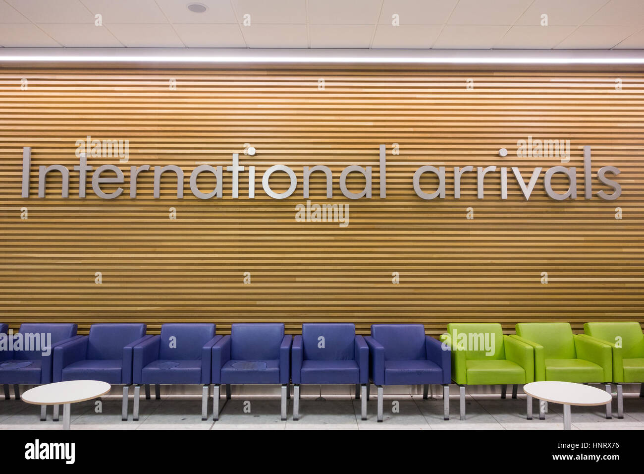 International Arrivals sign above row of empty chairs - Stock Image