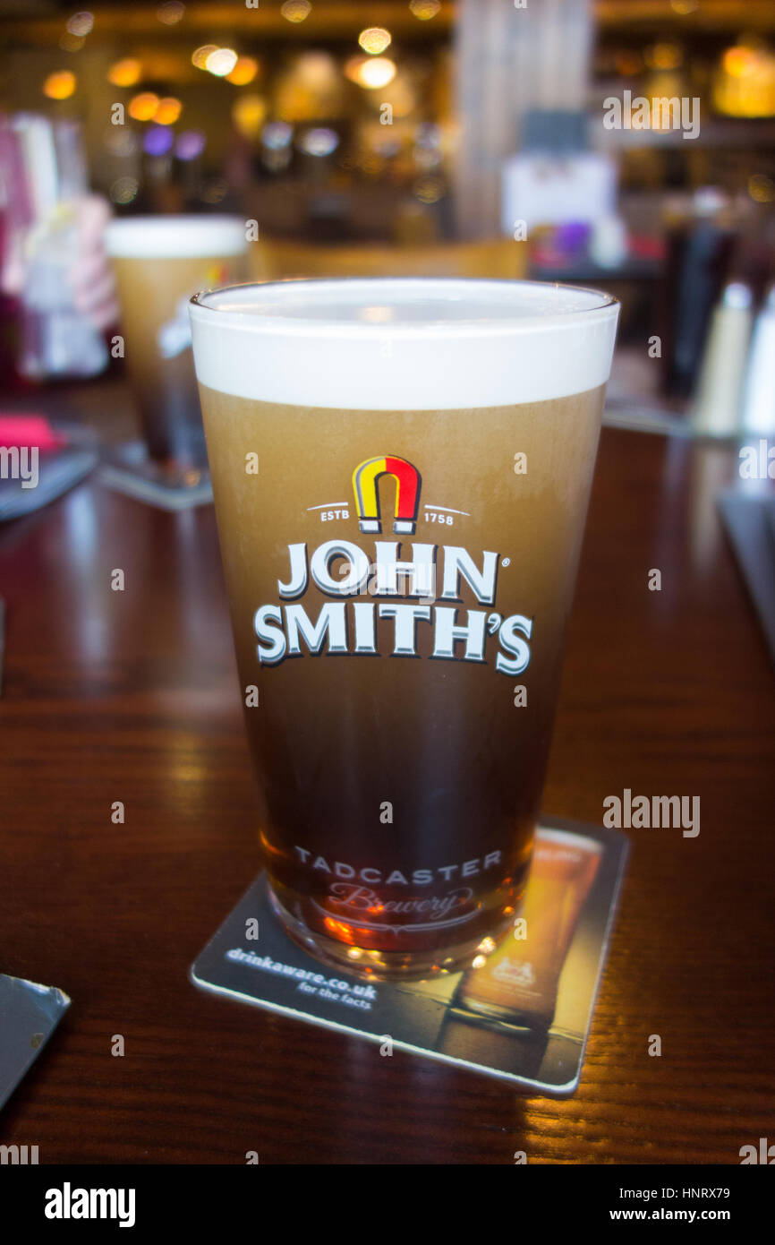 A pint of John Smiths bitter settling in a Yorkshire bar on a drinkaware beer mat - Stock Image