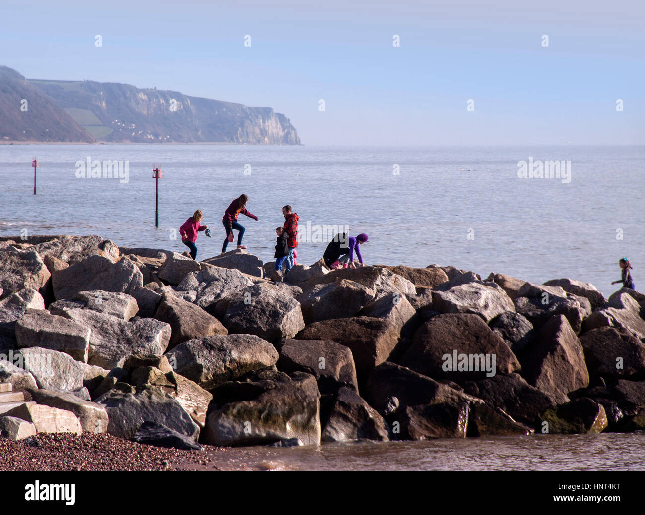 Sidmouth, Devon, UK. 16th Feb 2017. Half term playtime on the rock groynes at Sidmouth, Devon. Photo: South West - Stock Image
