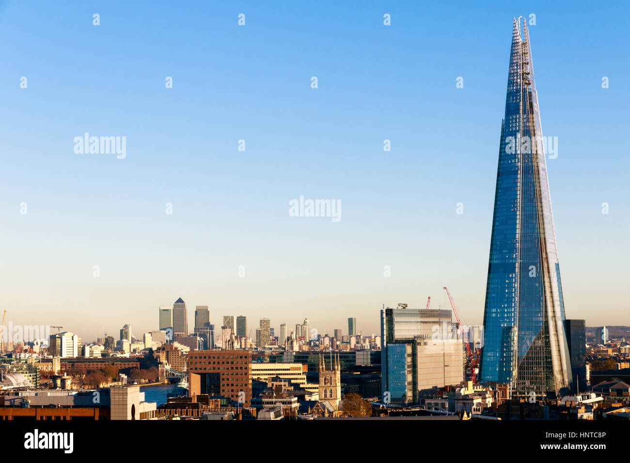 Financial district cityscape of London, including Canary Wharf and The Shard against a blue cloudless sky - Stock Image