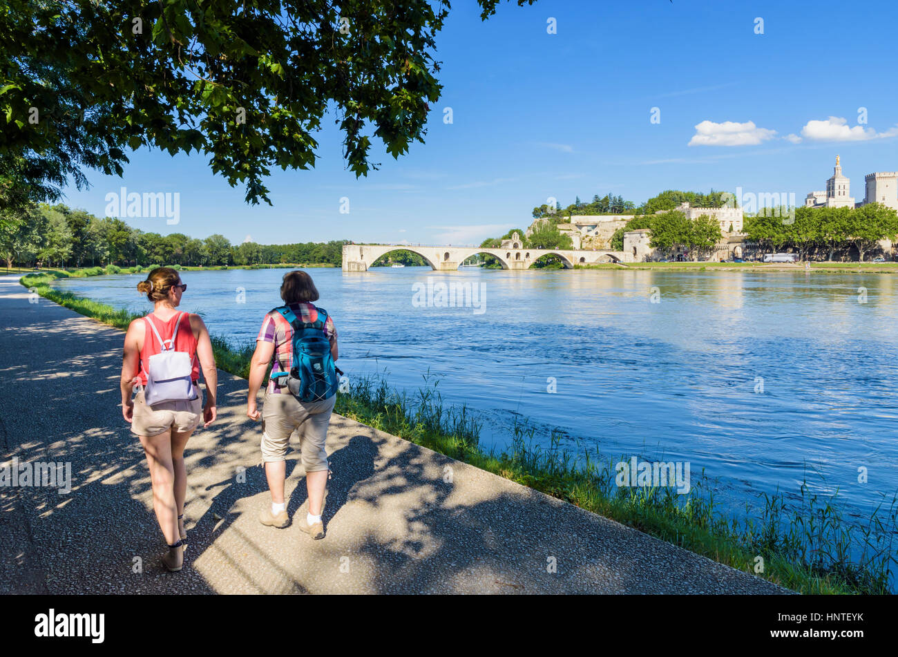 Avignon tourists walking along the Rhone River looking towards the Pont Saint-Bénézet bridge, Avignon, - Stock Image