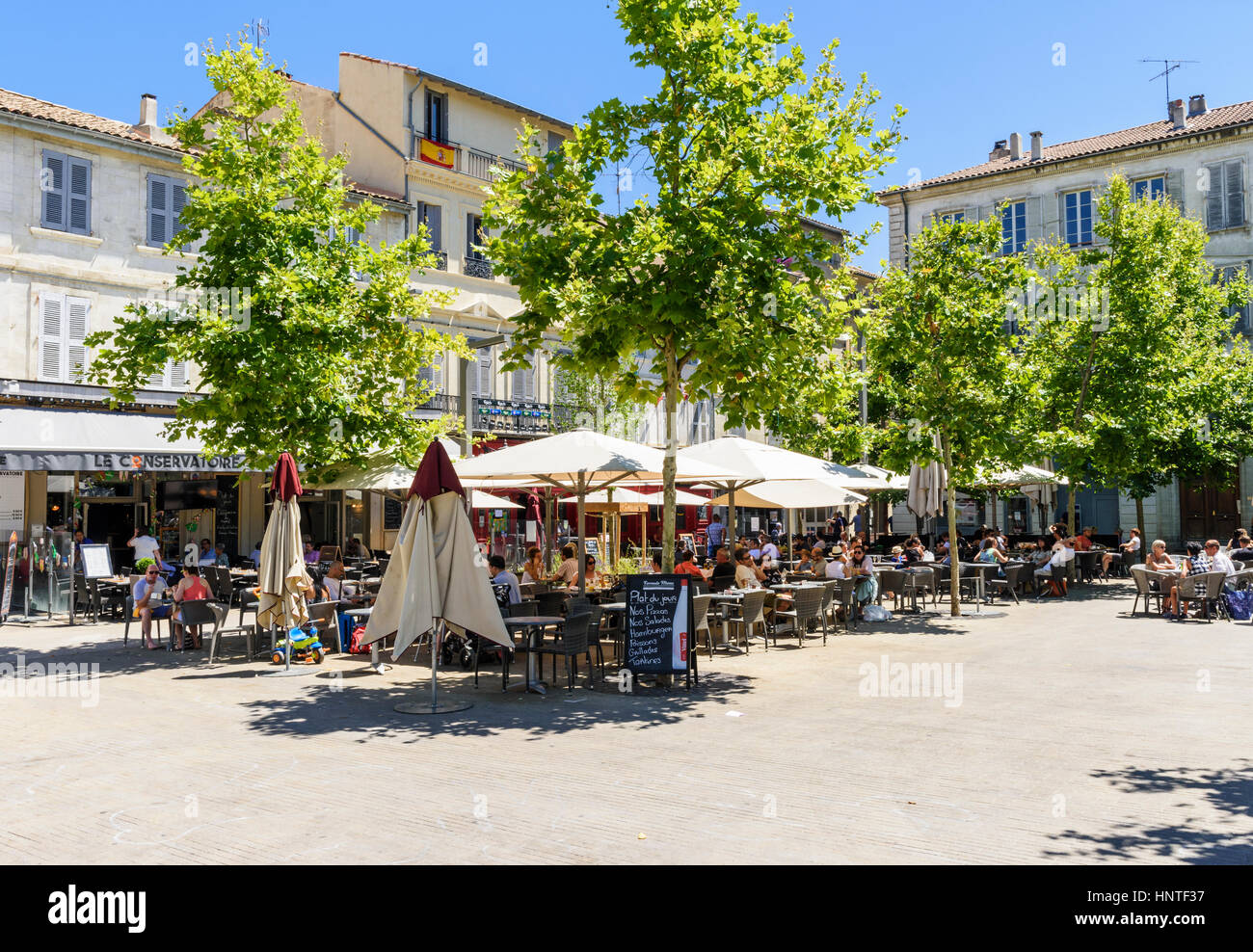 People seated at cafes and restaurants in Place Pie, Avignon, France - Stock Image