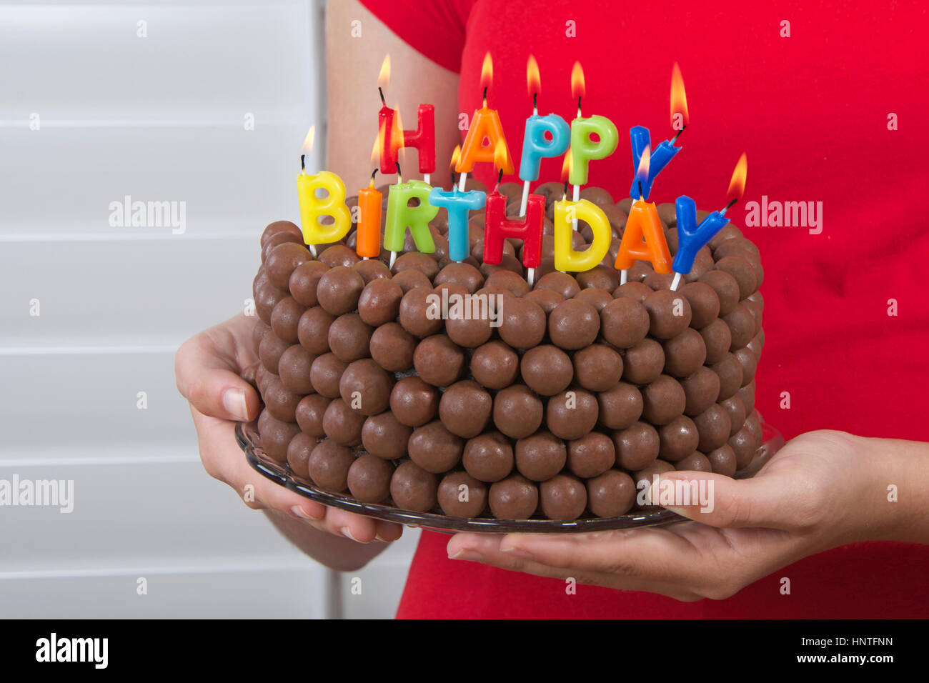 Young girl holding Chocolate Birthday Cake decorated with candy malt