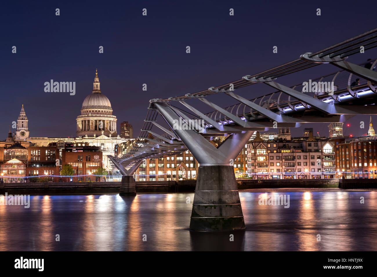 Night time view of the Millennium Bridge and River Thames, London, UK, with St Paul's Cathedral, lit up on the opposite Stock Photo